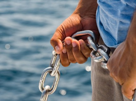 hands holding anchor chain on boat